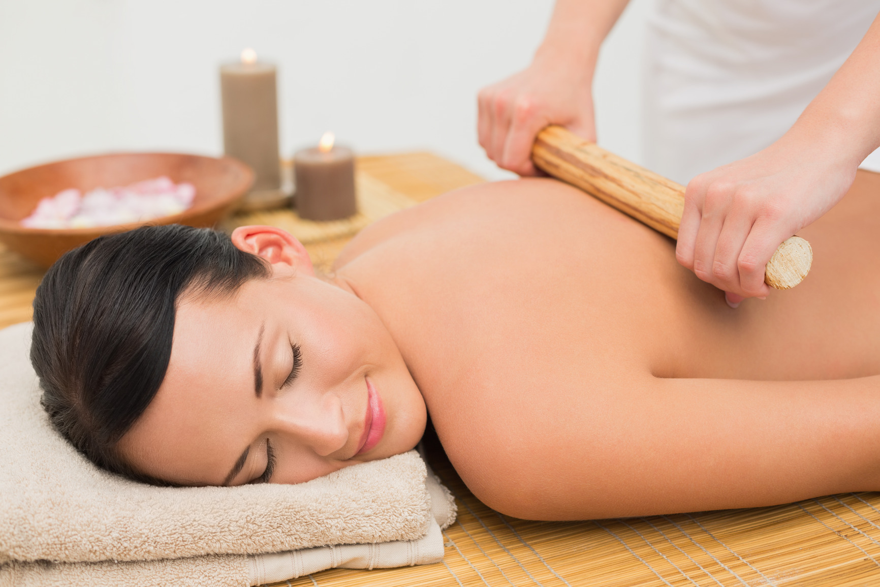 Beautiful brunette enjoying a bamboo roller massage in the health spa